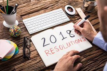 Fototapete - Businessman Writing 2018 Resolutions On Notebook