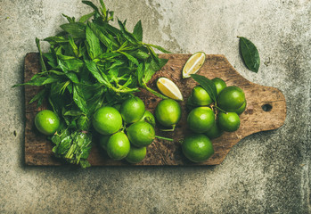 Flatlay of freshly picked organic limes and mint leaves for making cocktail or lemonade on wooden rustic board over grey concrete stone background, top view