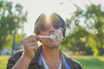 Man blowing soap bubbles in park