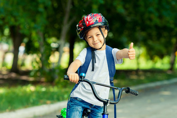 Little boy learns to ride a bike in thepark near the home. Kid shows the thumbs up on bicycle. Happy smiling child in helmet riding a cycling. Papier Peint