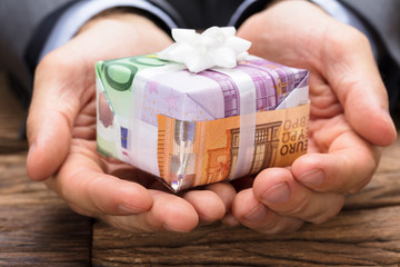 Businessman Holding Gift Box Made From Euro Papernotes