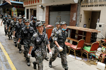 People's Liberation Army (PLA) soldiers walk on a damaged street after Typhoon Hato hits in Macau