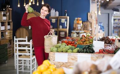 woman choosing artichokes in farm food store