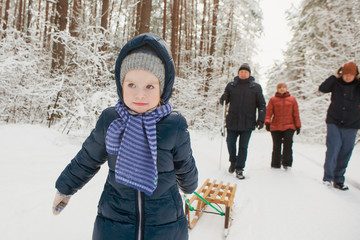 Happy girl child with family walk in winter snowy forest