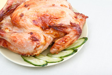 Grilled chicken and pieces of cucumber on white plate
