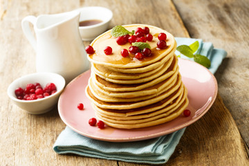 Homemade pancakes with berries and maple syrup