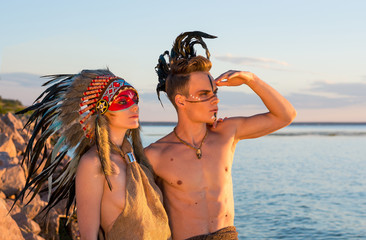 Man with an american indian coloring and feathers on his head embraces a woman dressed in american indian style on the seashore