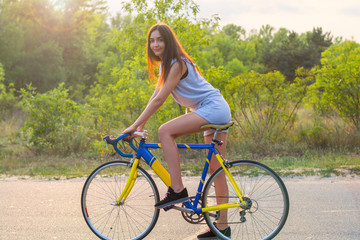 Young woman rides on a bicycle on the road in the park in the sunset rays of the sun