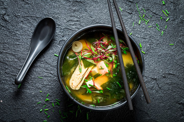 Photo sur Plexiglas Plat cuisine Hot and tasty miso soup with salmon on black rock