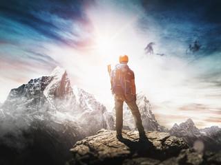 Bergsteiger mit Helm steht auf Berggipfel. Konzept für Erfolg.