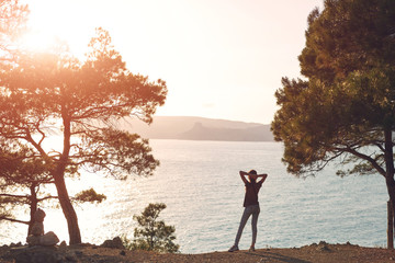 Back view of woman standing on the sea coast Between pines and Enjoying the sunset