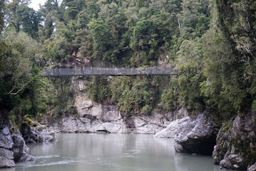 Rope bridge at Hokitika Gorge Walk with river under and forest background