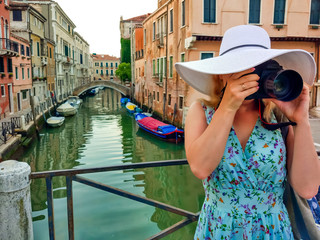 Close-up portrait of attractive woman taking pictures with her camera while discovering Venice.