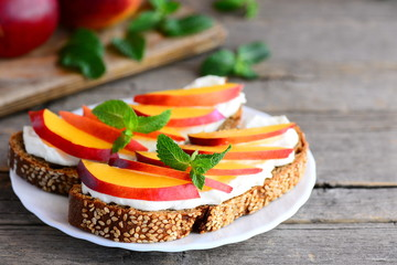 Cream cheese and fruit sandwich idea. Bright sandwiches with cream cheese, fresh nectarines slices, walnuts and mint on a serving plate and on a vintage wooden table. Rustic style. Closeup