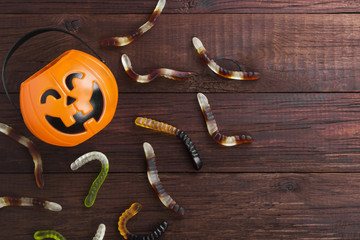 Terrible sweets (worms) for Halloween in decorative pumpkin on a dark background. Top view, copy space. Food background