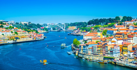 Beautiful panoramic view over Dom Luis I bridge and traditional boats on Rio Douro river in Porto, Portugal