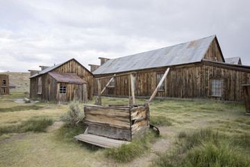 Wooden well and barn in field, Bodie