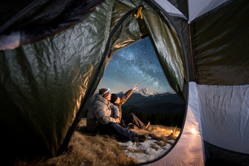 View from inside a tent on the two tourists have a rest in the camping in the mountains at night. Men sitting near campfire. One guy is pointing at the beautiful night sky full of stars and milky way