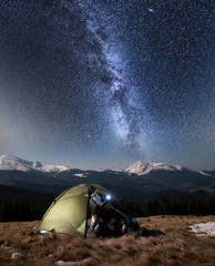 Male hiker have a rest in his camping in the mountains at night. Man with a headlamp sitting near tourist tent under beautiful night sky full of stars and milky way, and enjoying night scene