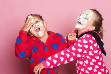 Girls in colorful polka dotted pajamas. Children with beauty masks