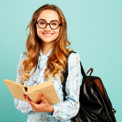 Pretty smiley girl wearing glasses pretty student holding books and wearing glasses over blue background