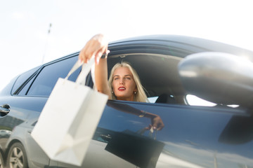 Girl with shopping in car