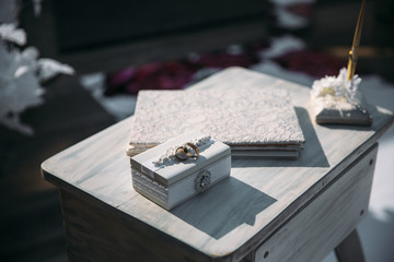 Wedding gold rings on a decorative white box, lie on the table. Jewelry concept