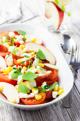 Refreshing tomato, corn, peach and feta salad with honey and mint dressing. Selective focus, close up.