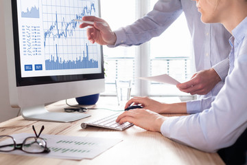 Traders with forex trading charts and graphs on computer screen
