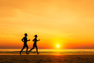 Silhouette of active sporty couple running on the beach, sunset