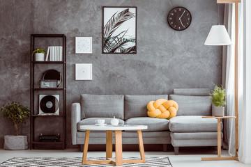 Black clock above grey settee