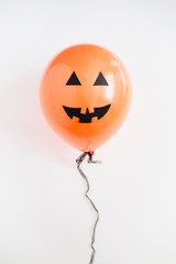 Halloween minimal concept. One orange balloon with funny smiling face on white background. Flat lay, top view.