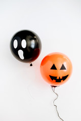 Halloween minimal concept. Two balloons with funny smiling and scary faces on white background. Flat lay, top view.