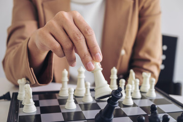 Close up of hands confident businesswoman playing chess game to development analysis new strategy plan, leader and teamwork concept for success