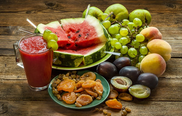 Watermelon smoothies, pieces of watermelon and other fruits on a wooden table