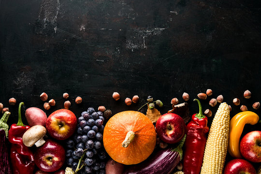 Different seasonal autumn vegetables and fruits on green wooden background