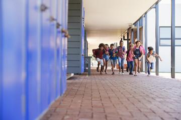 School kids running to camera in elementary school hallway