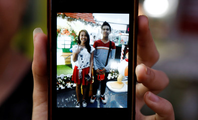 Shirley, sister of Kian Loyd delos Santos, a 17-year-old student who was shot during an anti-drug operations, shows her picture with her brother on a cell phone in Caloocan, Metro Manila
