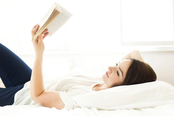 Young woman reading book while lying on bed