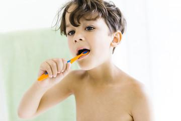 Shirtless boy brushing teeth