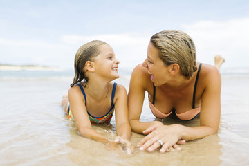 Mother lying with daughter (6-7) on beach