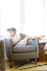 Young girl (6-7) sitting on armchair and using mobile phone