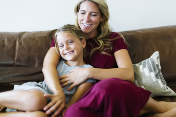 Woman sitting with daughter (6-7) on couch