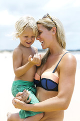Mother with son (4-5) embracing at beach