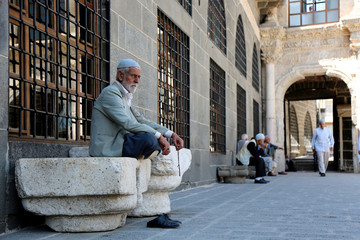 Men wait for Friday prayers at the courtyard of Ulu mosque in the Kurdish-dominated city of Diyarbakir