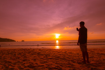 silhoutte man using mobile phone take photo during sunset