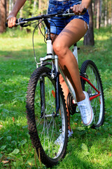 Woman on a bike in summer forest