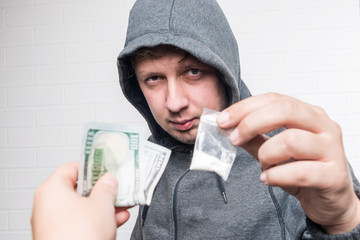 Portrait of a drug dealer with drugs and a female hand with money