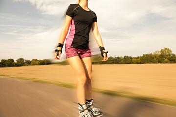 Frau läuft Inlineskates auf Feldweg
