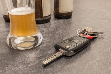 Bier in einem Glas und Autoschlüssel auf dem Tisch und leere Bierflaschen im Hintergrund